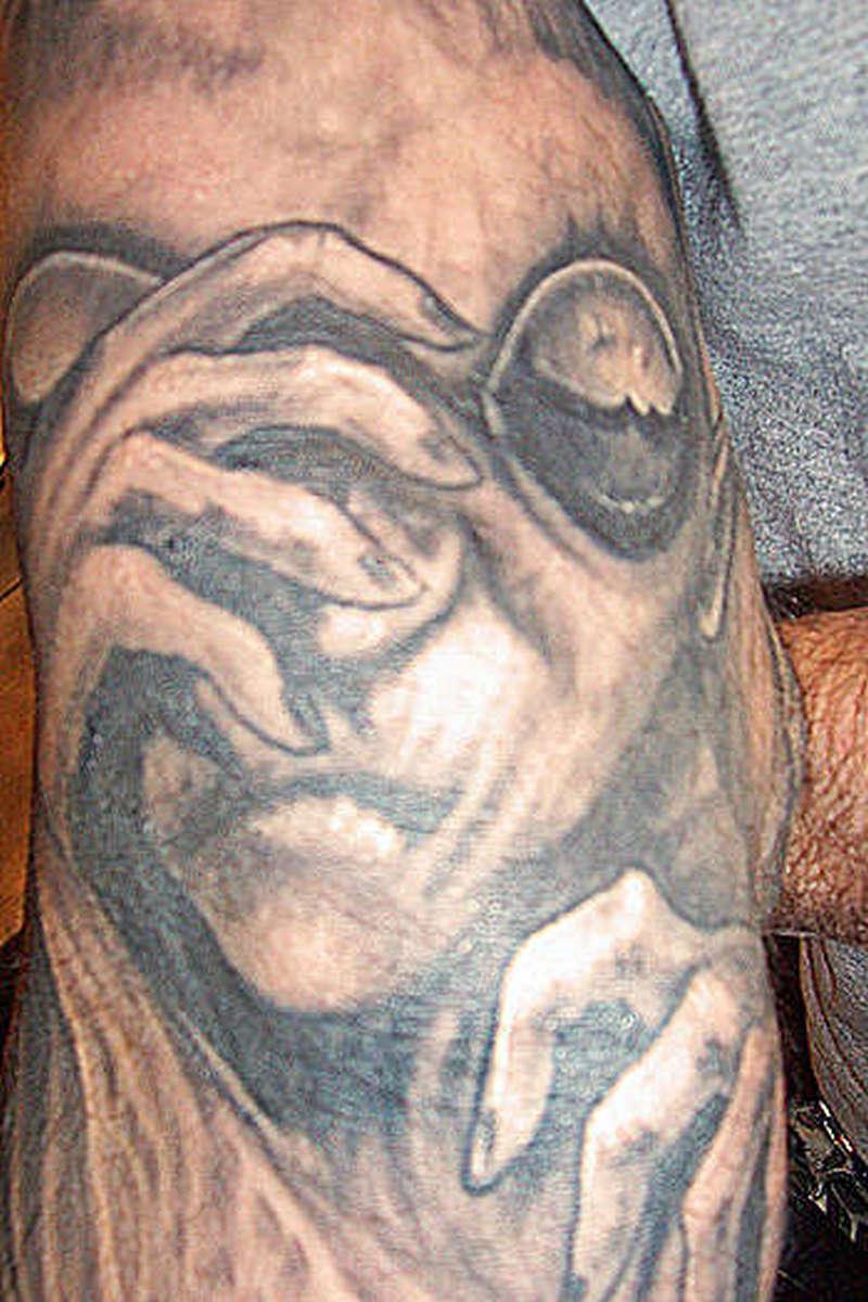 Alien sad face tattoo
