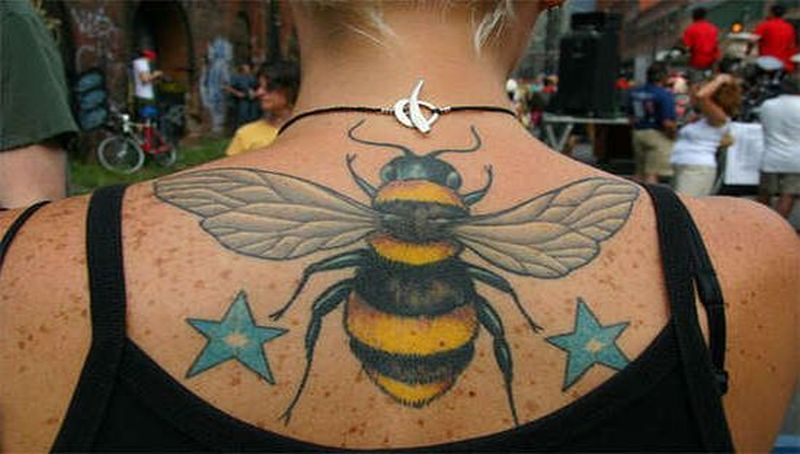 Bee tattoo on upper back with stars