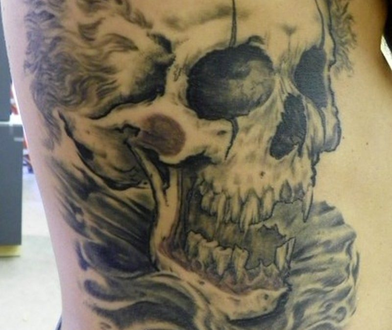 Big clown skull tattoo on rib side