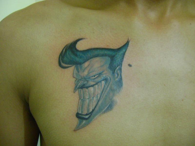 Big teeth joker face tattoo on chest