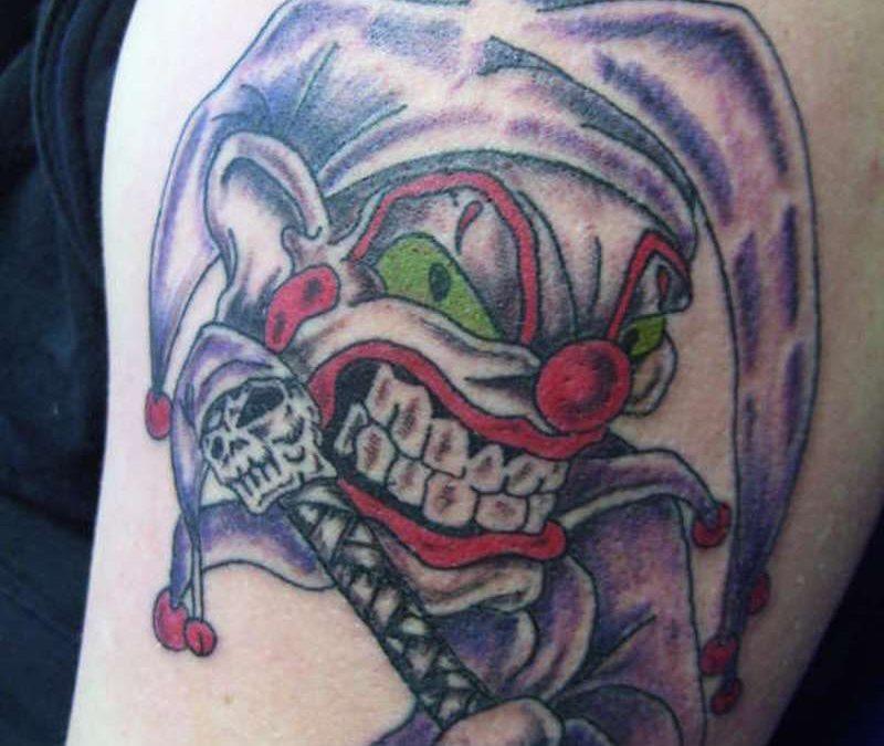 Big teeth joker tattoo on biceps