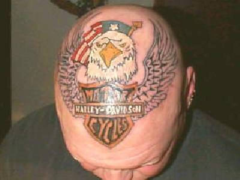 Biker having harley bike tattoo on skull