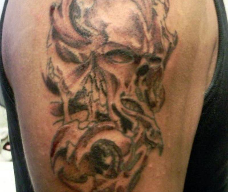 Biomechanical horror skull tattoo on biceps