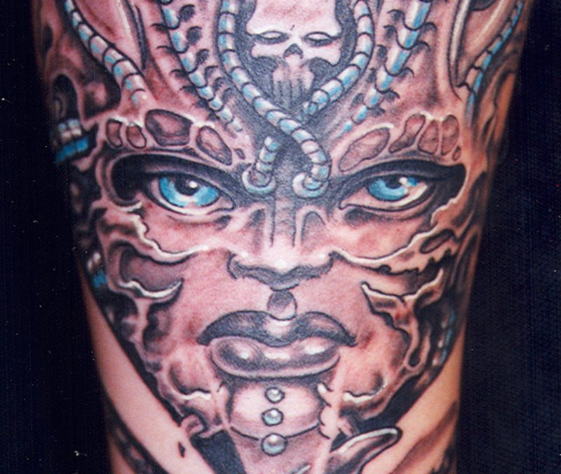 Biomechanical mask on female with skulls tattoo