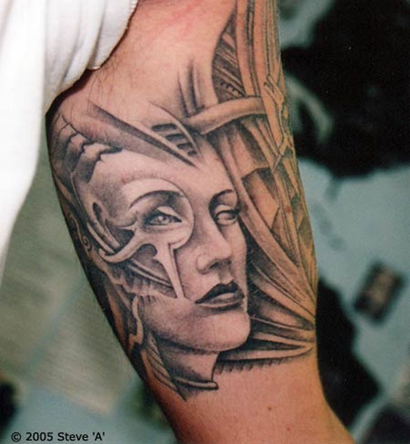 Biomechanical womans face inner biceps tattoo