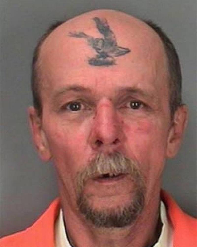 Bird tattoo on forehead of old guy