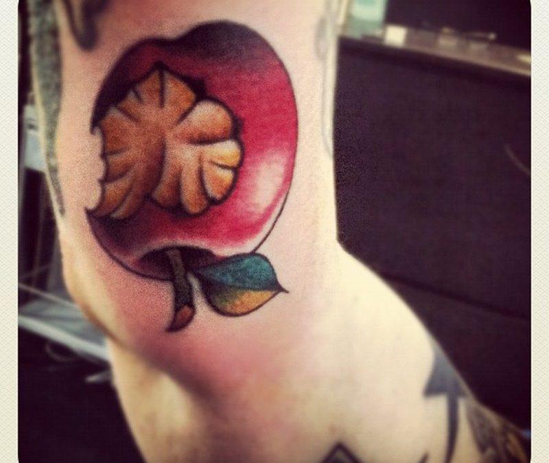 Bitten apple tattoo on elbow