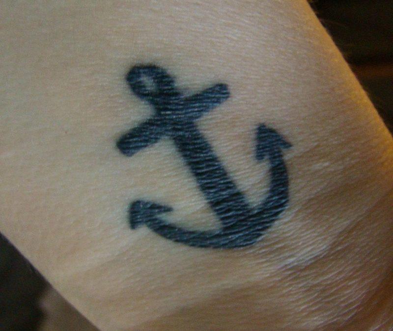 Black anchor tattoo on wrist