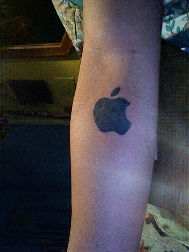 Black apple logo tattoo on arm