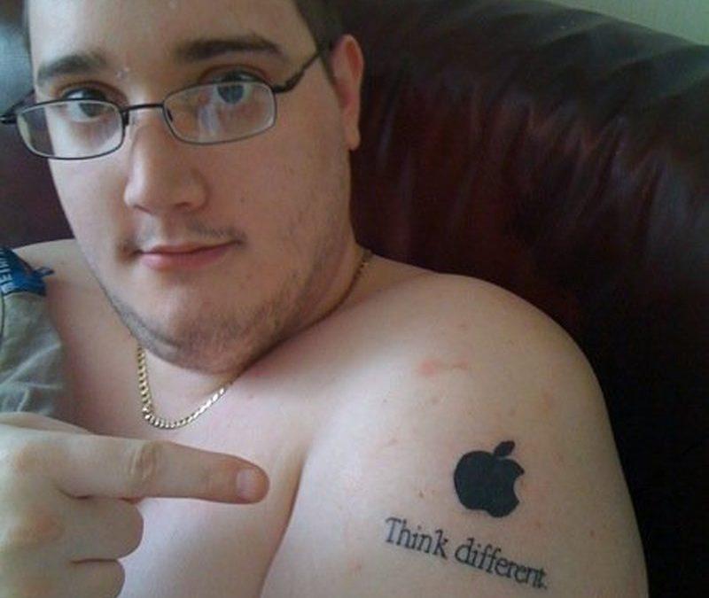 Black apple logo tattoo on mans shoulder