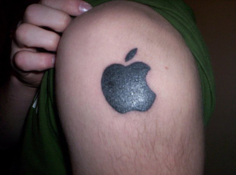 Black apple logo tattoo on shoulder