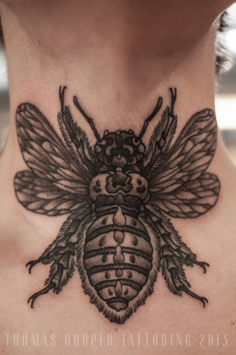Black bumblebee tattoo on neck