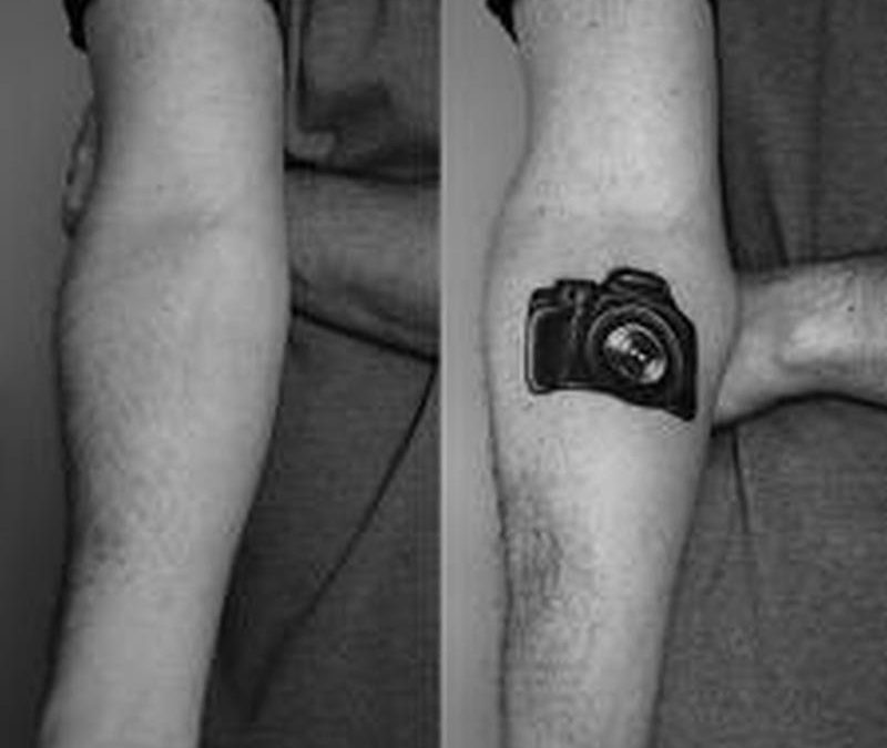 Black camera tattoo on forearm