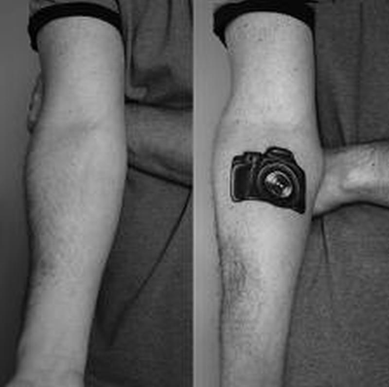 Black camera tattoo on forearm