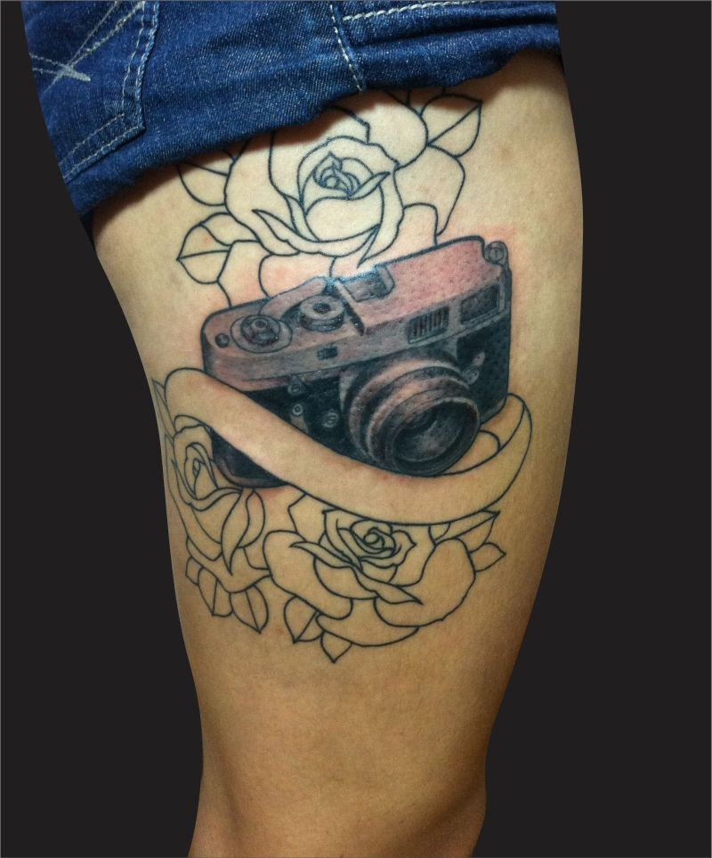 Black camera tattoo on thigh