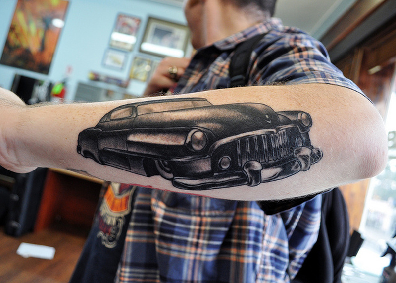 Black car tattoo on forearm