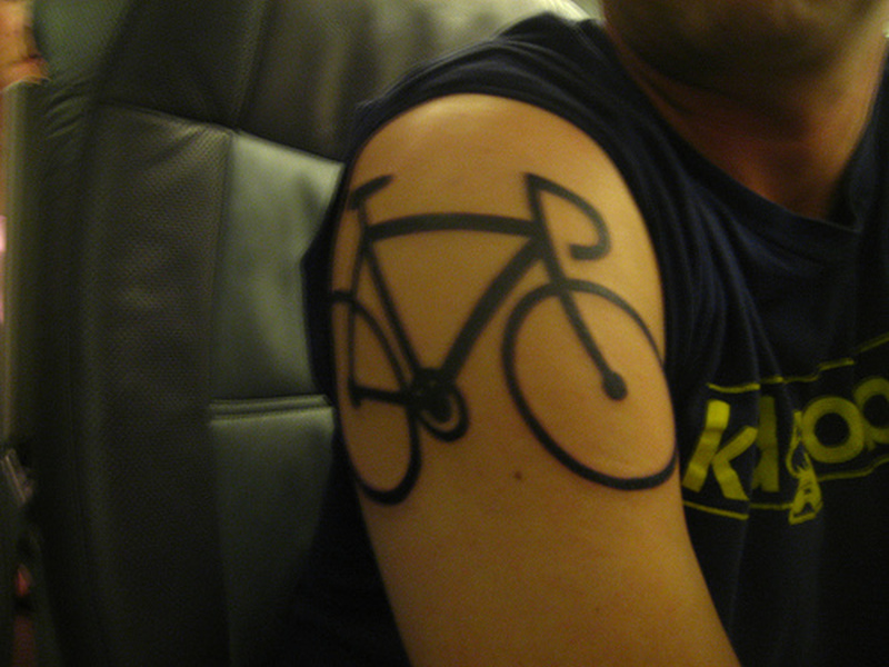 Black cycle tattoo on shoulder
