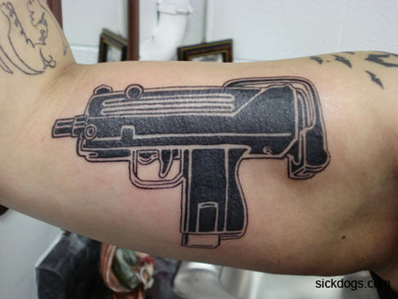 Black gun tattoo on muscles