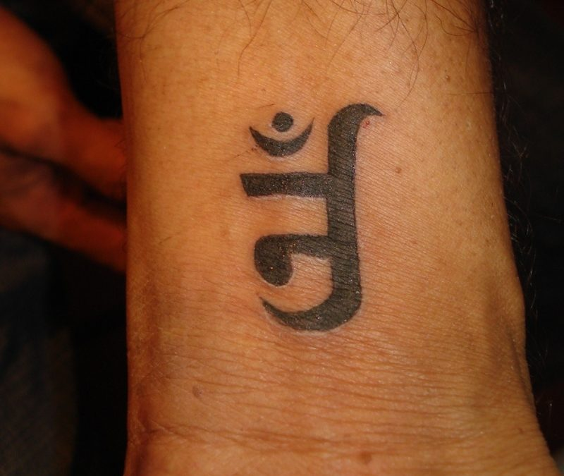 Black ink jain om tattoo on wrist