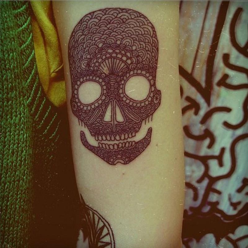 Black ink pattern skull tattoo on forearm