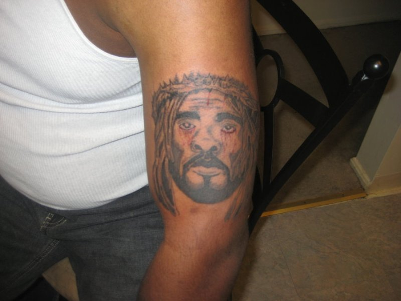 Black jesus with dreads tattoo on muscles