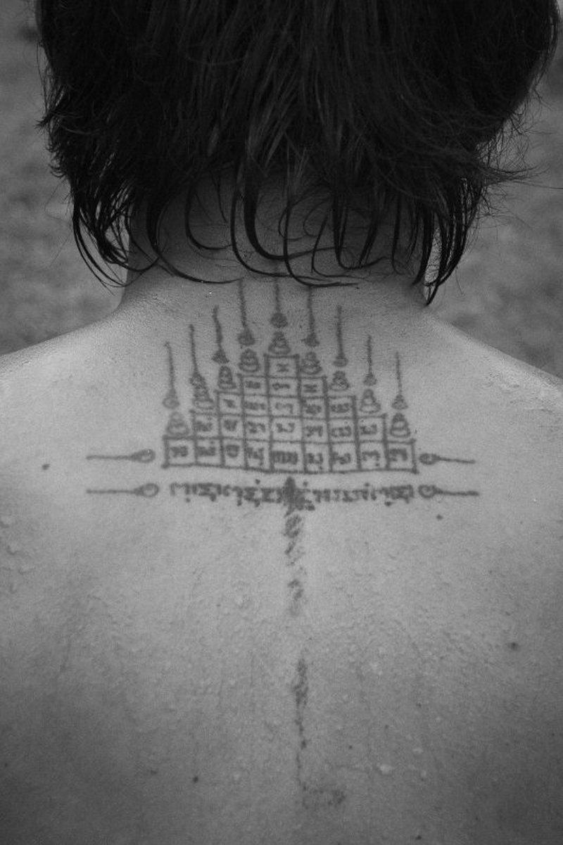 Black white religious buddhist tattoo on upper back