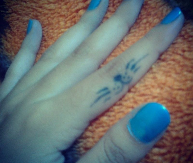 Blue cat tattoo on finger