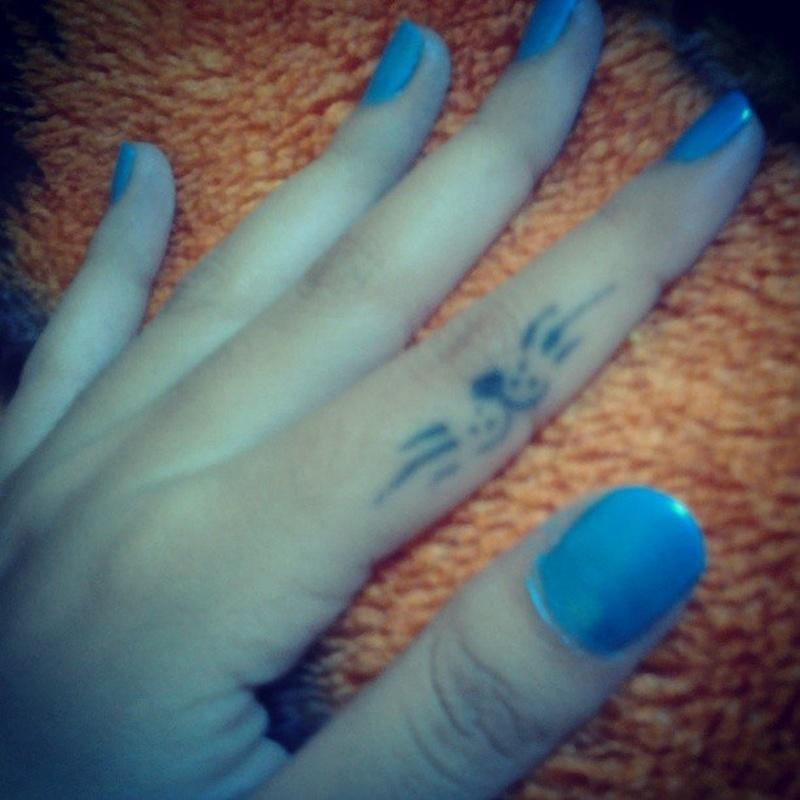 Blue cat tattoo on finger