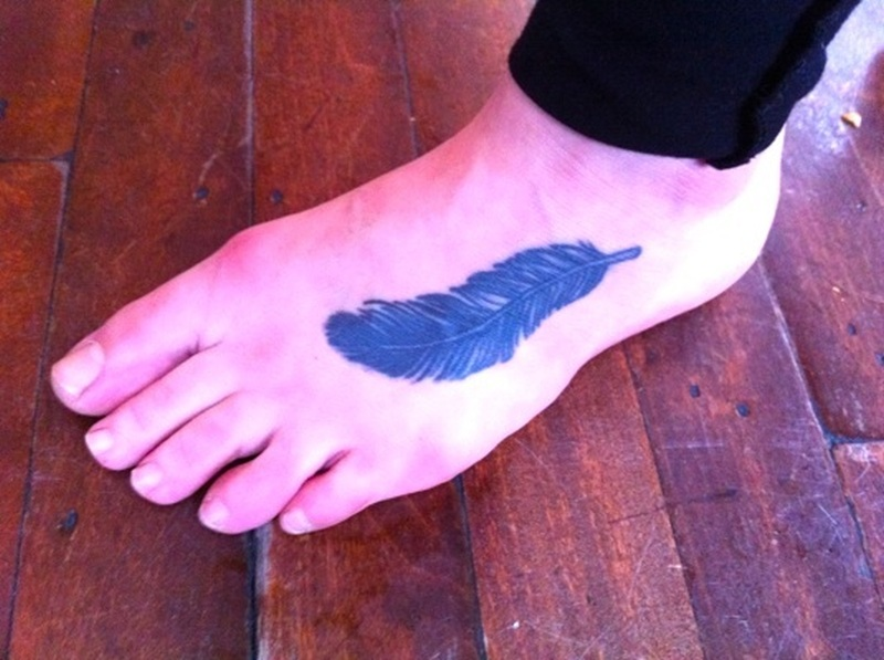 Blue feather tattoo on foot