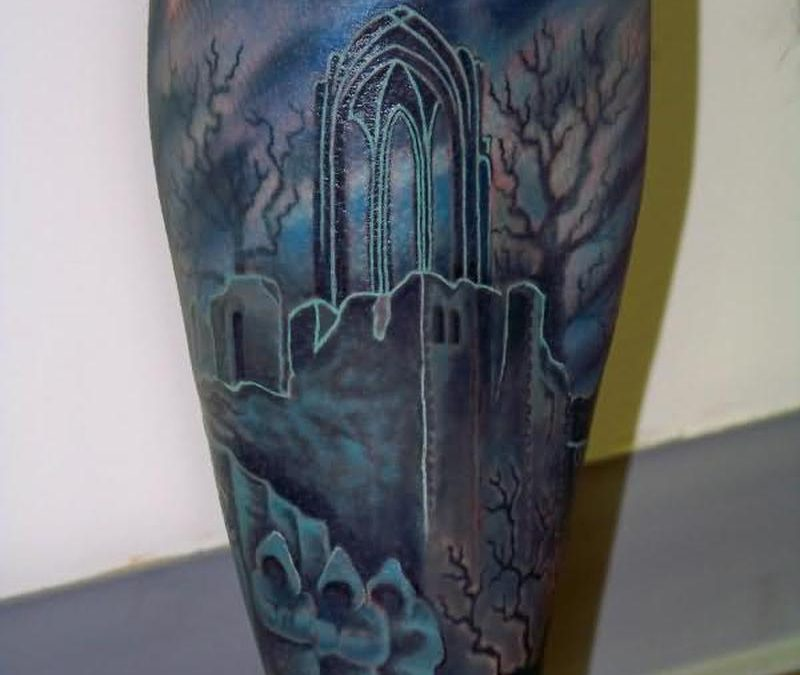 Blue ink graveyard tattoo design on leg