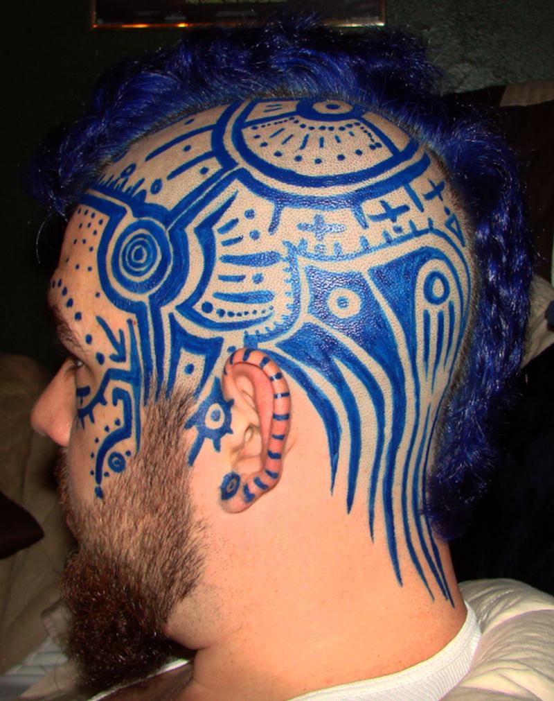 Blue ink tribal tattoo on head