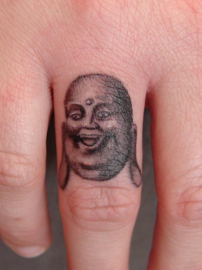 Buddha face tattoo on finger
