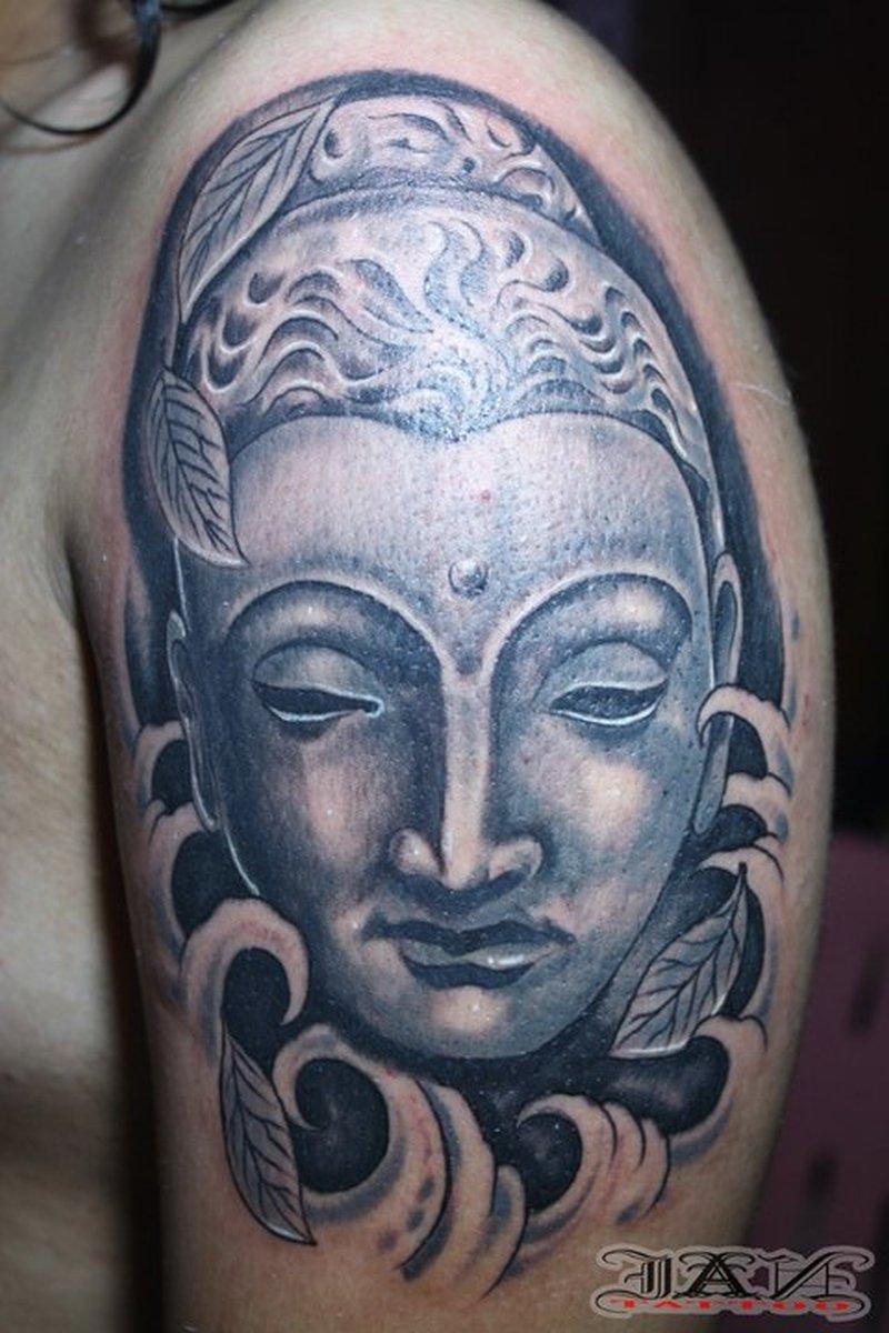 Buddha head tattoo on biceps