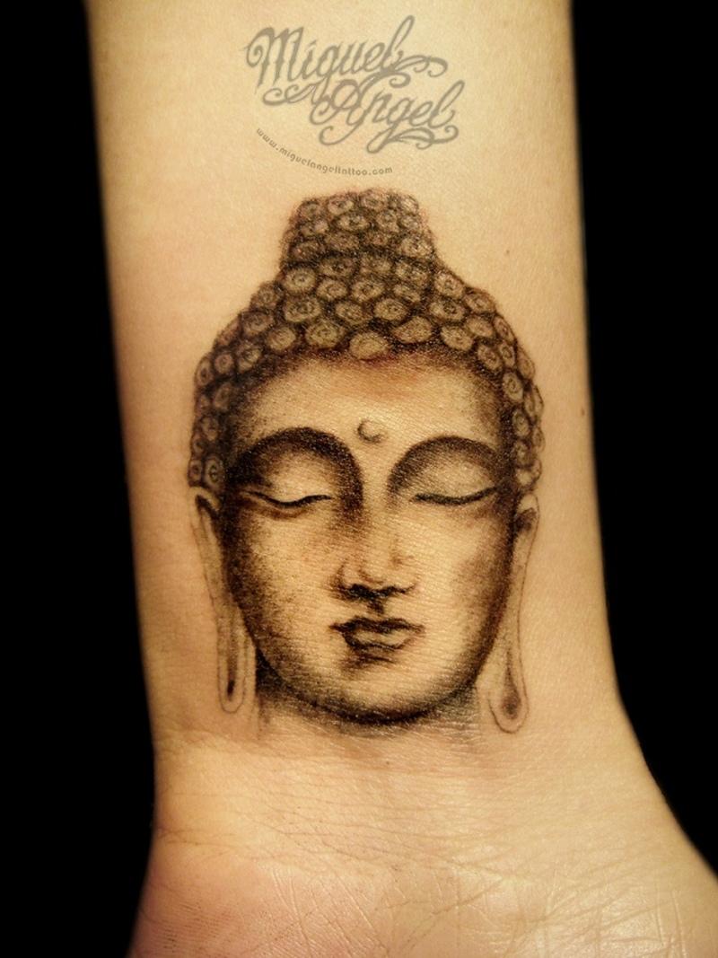 Buddha head tattoo on wrist