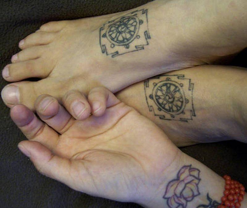 Buddhist wheel tattoo on feet