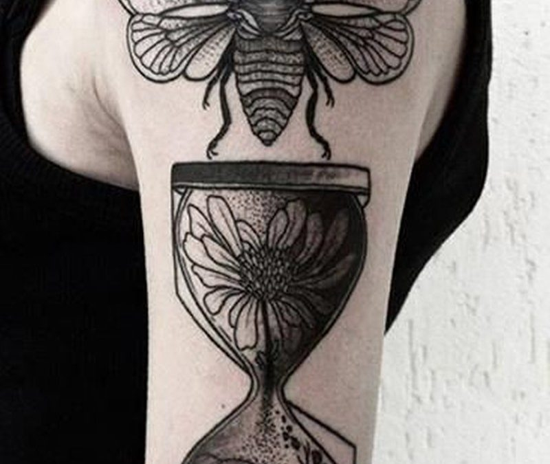 Bug and hourglass black ink tattoo on half sleeve