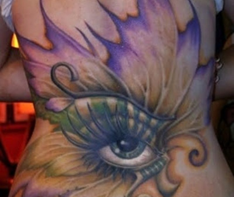 Butterfly eye tattoo on lower back
