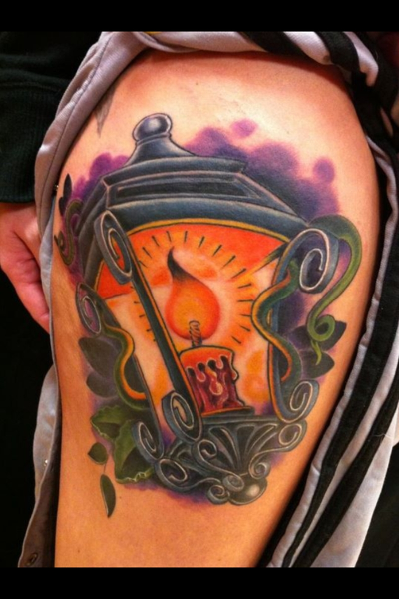 Candle lantern tattoo on biceps