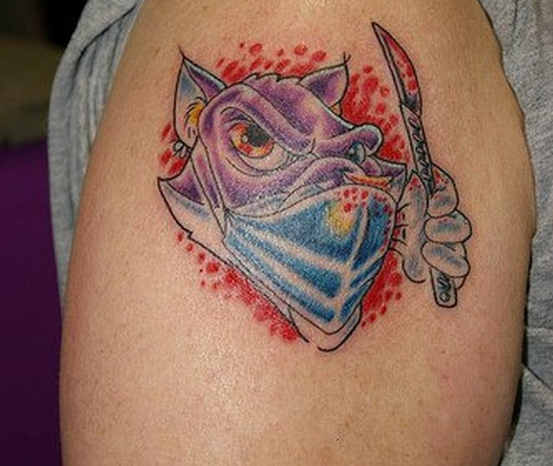 Cartoon dog with knife tattoo on shoulder