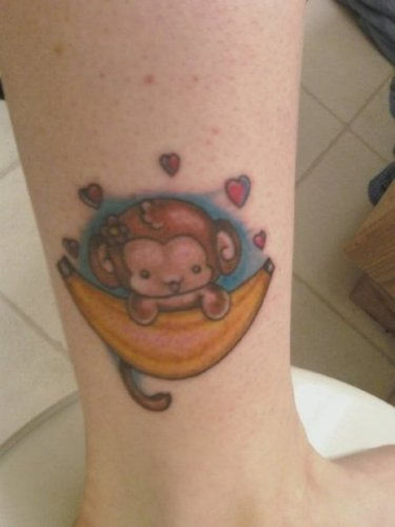 Cartoon monkey on banana ankle tattoo