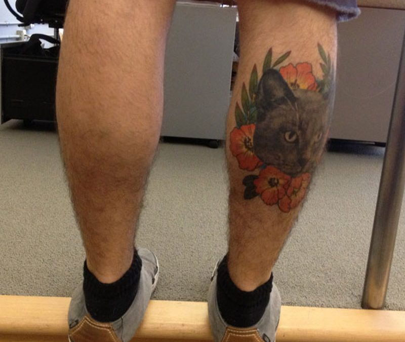 Cat face with flowers tattoo on knee