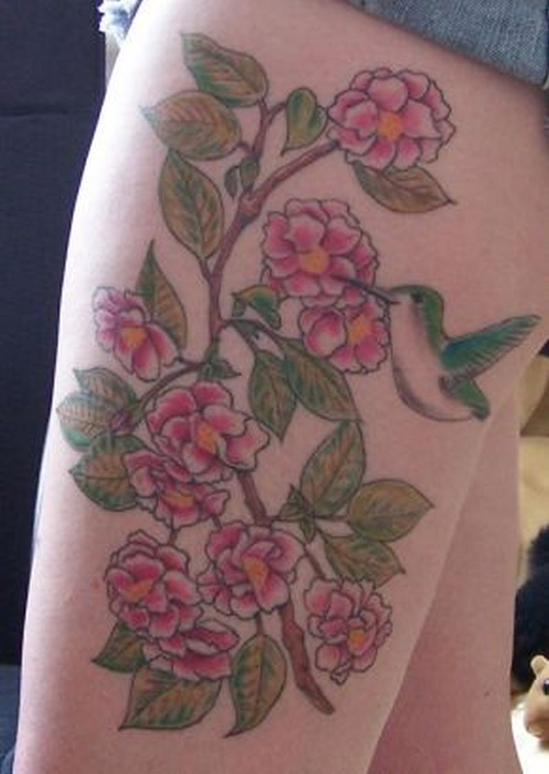 Cherry blossom and hummingbird tattoo on thigh