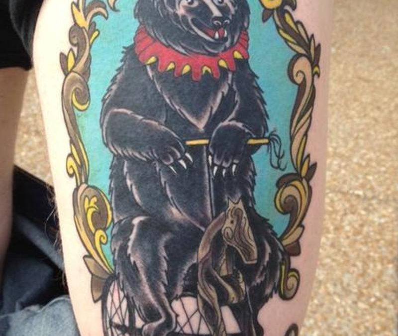 Circus bear tattoo on thigh