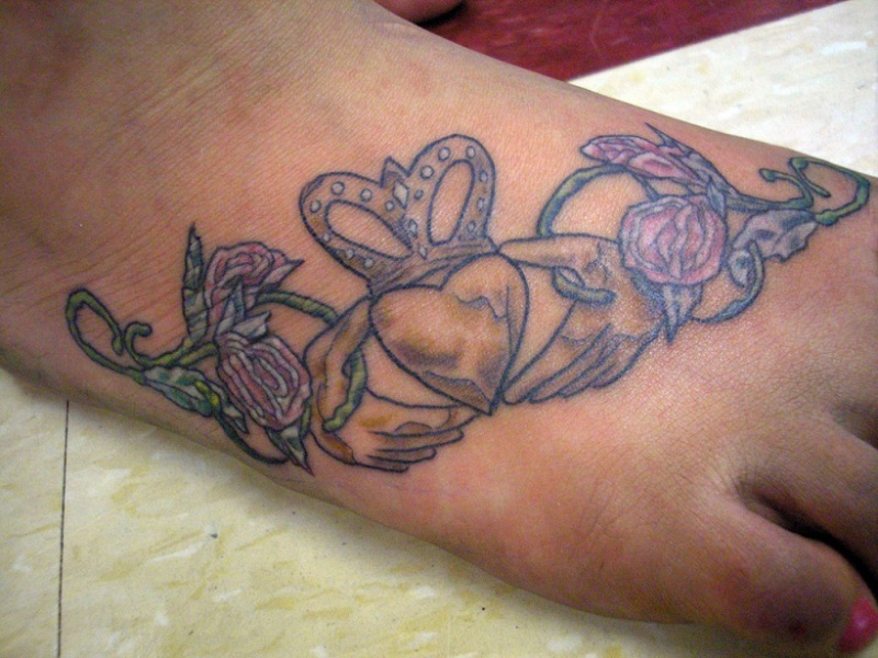 Claddagh foot tattoo with flowers