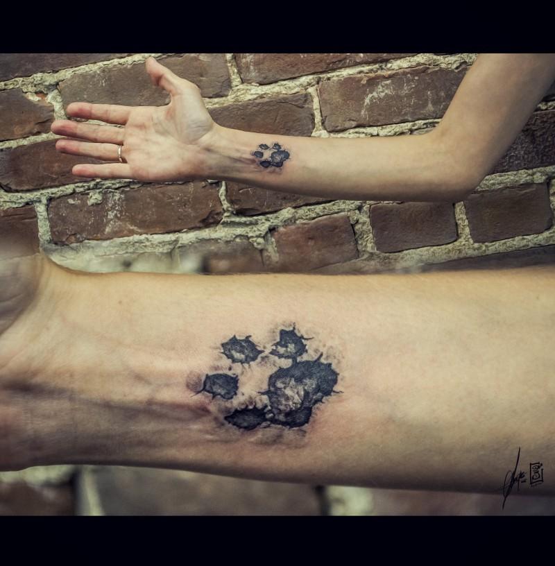Classic paw print dog forearm tattoo