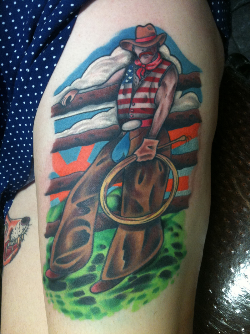 Colorful cowboy tattoo on thigh