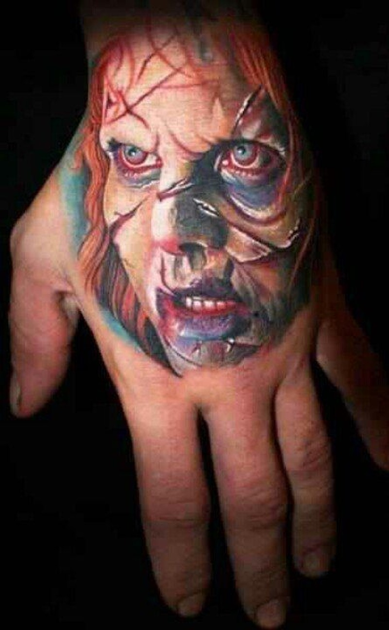 Colorful exorcist movie horror tattoo on hand
