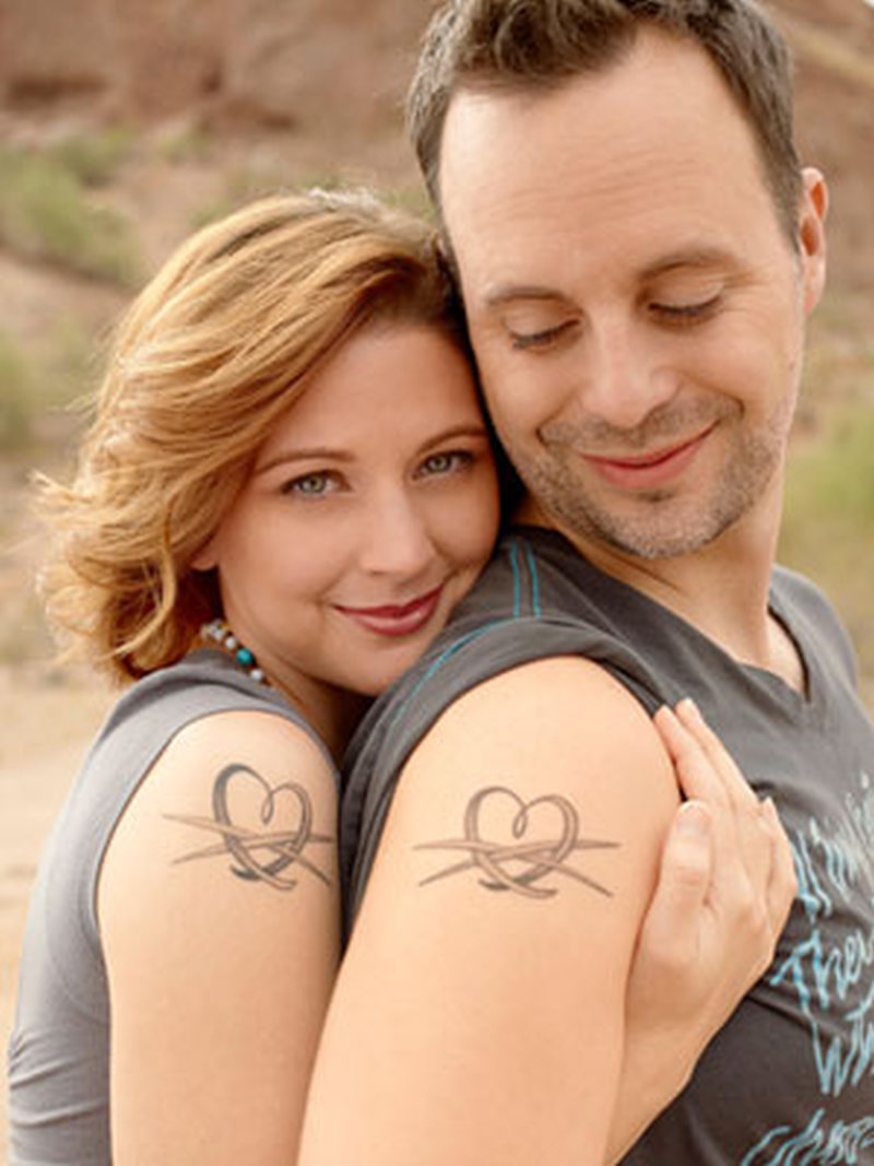Couple with hearts tattoo on shoulder