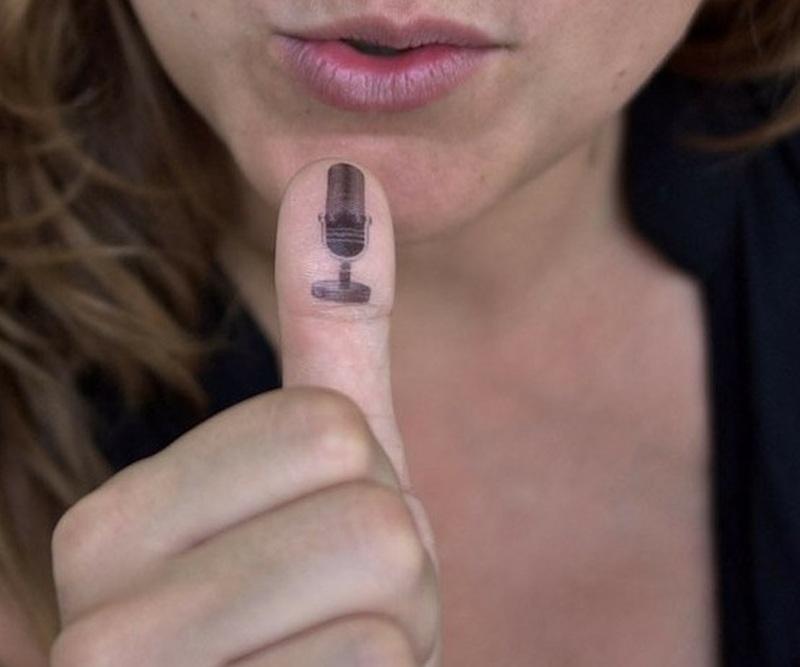 Creative funny tattoo on thumb top