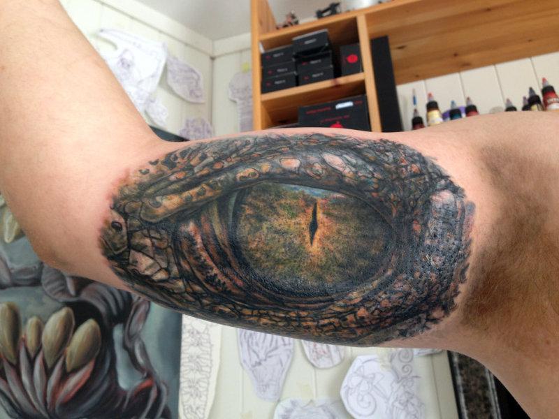 Crocodile eye tattoo on muscles